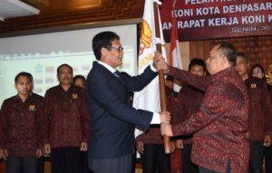 Ketut Suwandi menyerahkan bendera KONI kepada Toni Astawa